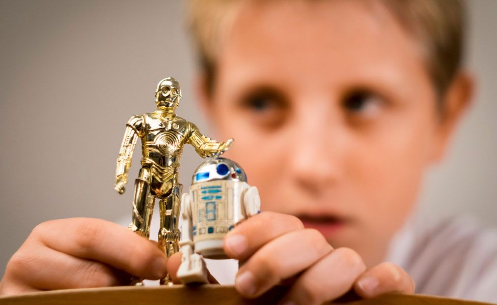 A boy playing with two Star Wars figures
