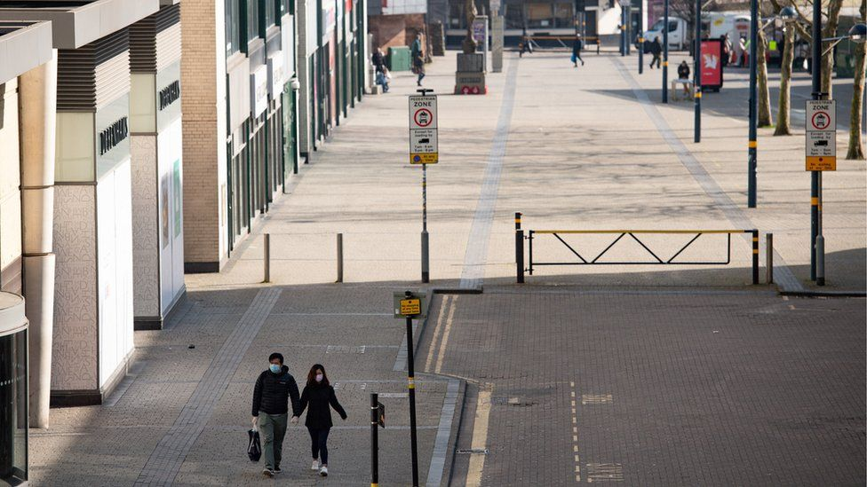 A couple wearing protective equipment walk by the Bullring in Birmingham, the day after Prime Minister Boris Johnson put the UK in lockdown to help curb the spread of the coronavirus