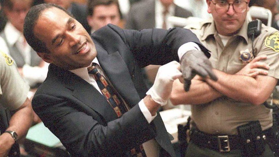 Double murder defendant O.J. Simpson puts on one of the bloody gloves as a Los Angeles Sheriff's Deputy looks on during the O.J. Simpson murder trial 15 June. One of the gloves was found at the murder scene, while the other was found at Simpson's state.