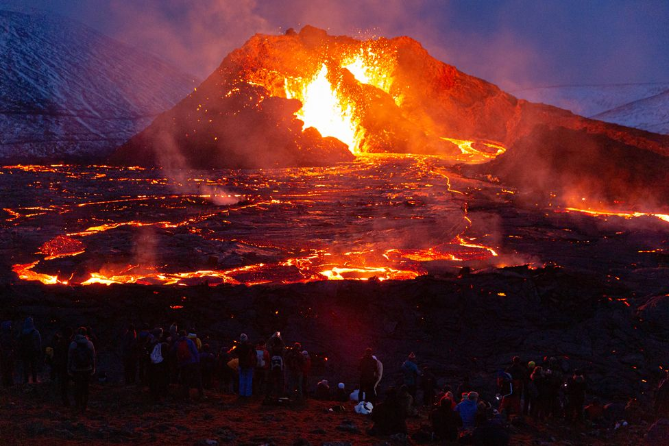 People are illuminated by the glow of lava from Mount Fagradalsfjall in Iceland, on 28 March 2021