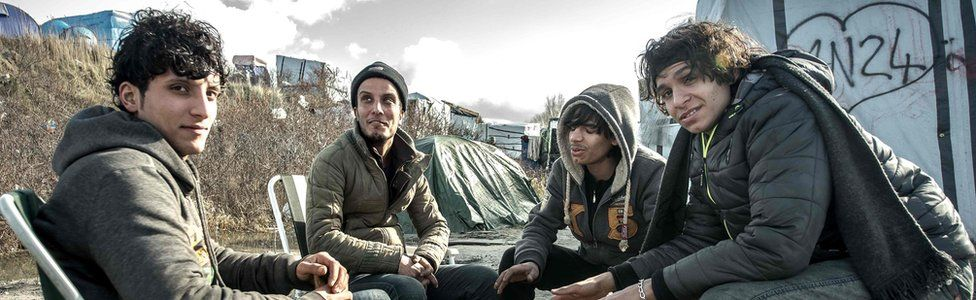 Young men sit around a fire on 19 February 2016 in the Jungle camp of migrants and refugees in Calais, northern France