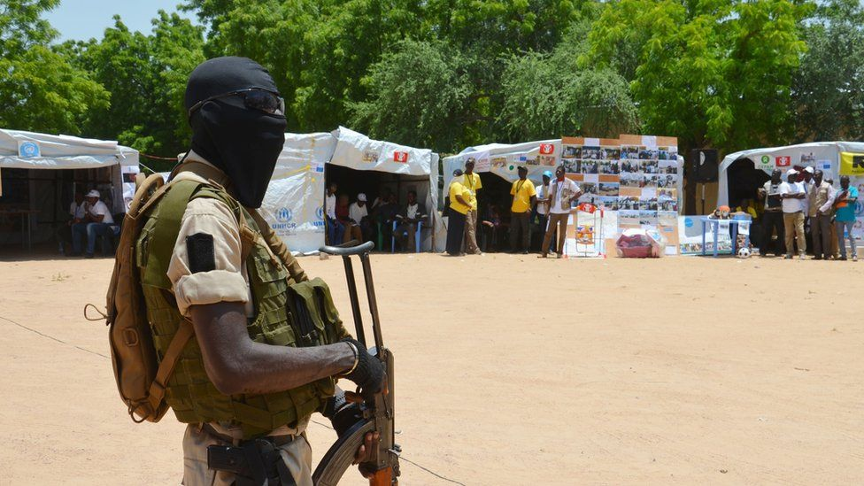 A Niger soldier stands guard near information stands in a camp for internally displaced people in Diffa, Niger, in 2016