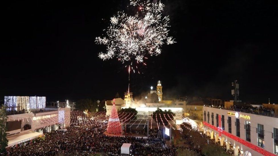 People celebrate during the lighting ceremony of a Christmas tree outside the Church of Nativity in the West Bank city of Bethlehem. Photo: 2 December 2017