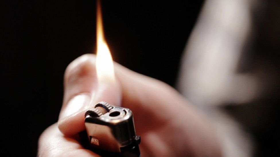 Person igniting disposable lighter