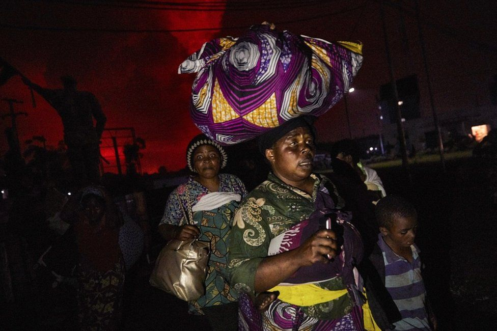 A Congolese woman, carrying possessions on her head, flees from Mount Nyiragongo volcano as it erupts over Goma, Democratic Republic of the Congo, on 22 May 2021