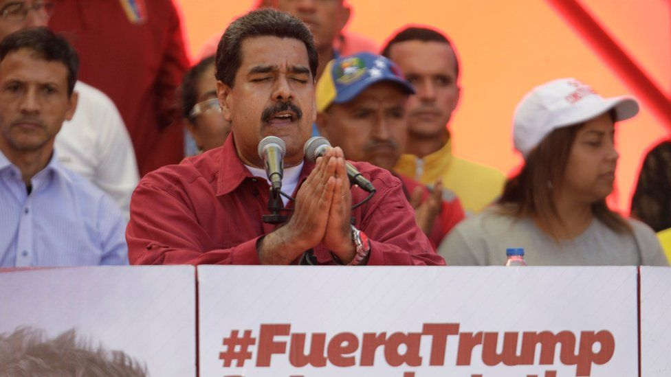 """President Nicolás Maduro gives a speech by a sign reading, """"Trump go away from Latin America"""" at a rally against President Donald Trump in Caracas, Venezuela, August 14, 2017"""