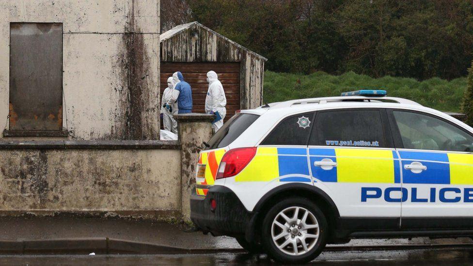 Forensic investigators at the building where Piotr Krowka's body was found