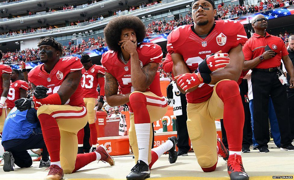 Eli Harold, Colin Kaepernick and Eric Reid kneel before a 49ers match