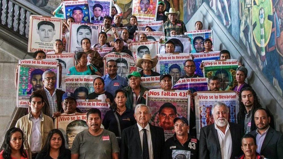A handout photo released by the Mexican presidency shows President Andres Manuel Lopez Obrador (C down) posing for a picture with relatives of some of the 43 students who disappeared, at the Palacio Nacional, in Mexico City on 11 September 2019