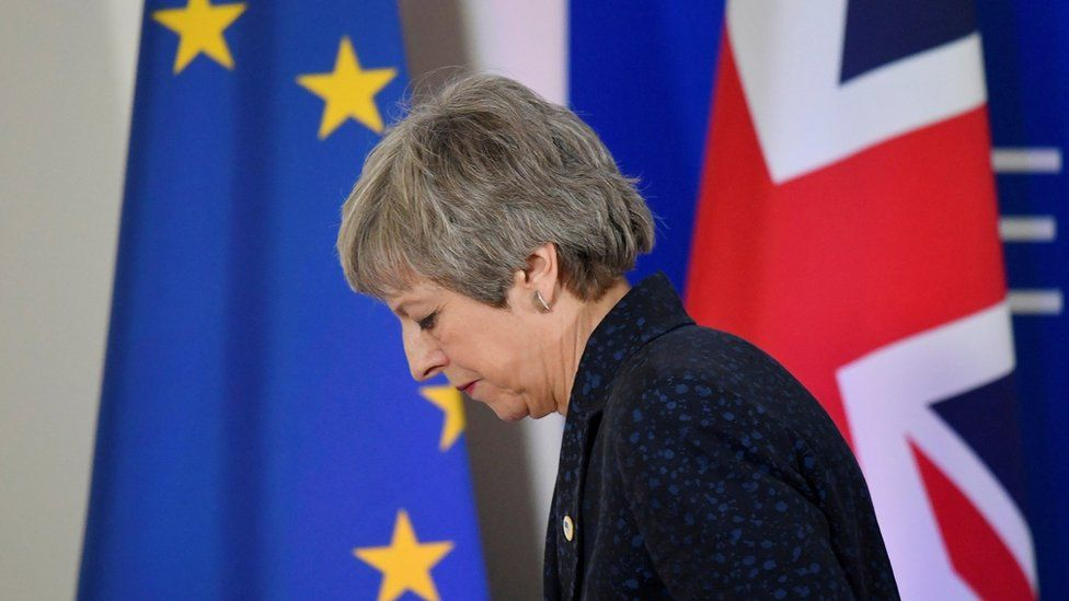File photo: Theresa May looks down as she walks in front of an EU flag and a UK flag, 22 March 2019