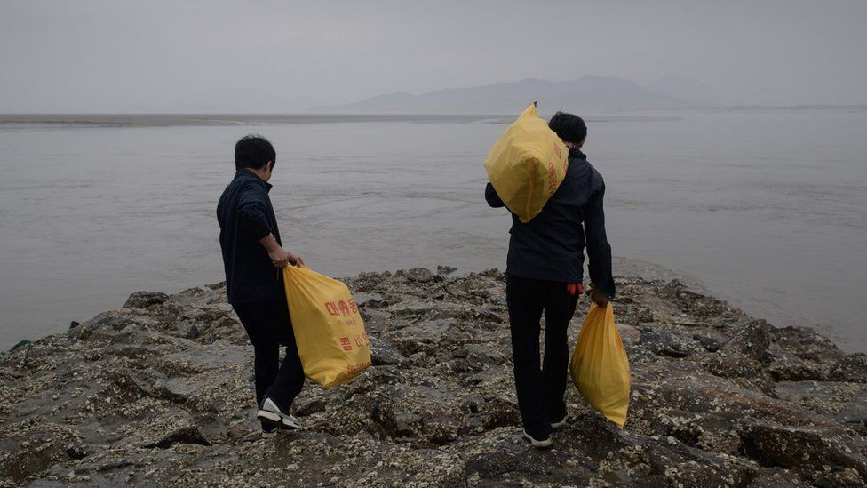 North Korean defector activists carry bags of bottles containing rice, money, and USB sticks, on Ganghwa island, west of Seoul on May 1, 2018.