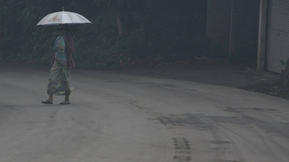 A woman uses an umbrella as she walks through ash from Mount Agung volcano in Bebandem Village, Karangasem, Bali, Indonesia on Sunday. Photo supplied by Antara Foto