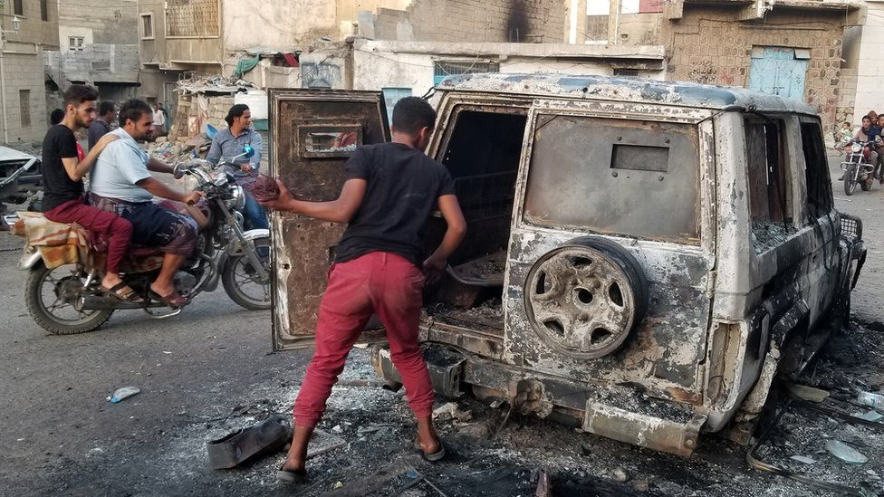 File photo showing a man looking at a burnt car in the Yemeni city of Taiz on 23 March 2019