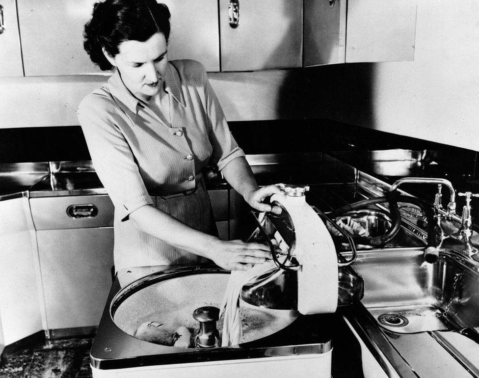 A woman demonstrating an early electric washing machine, circa 1950