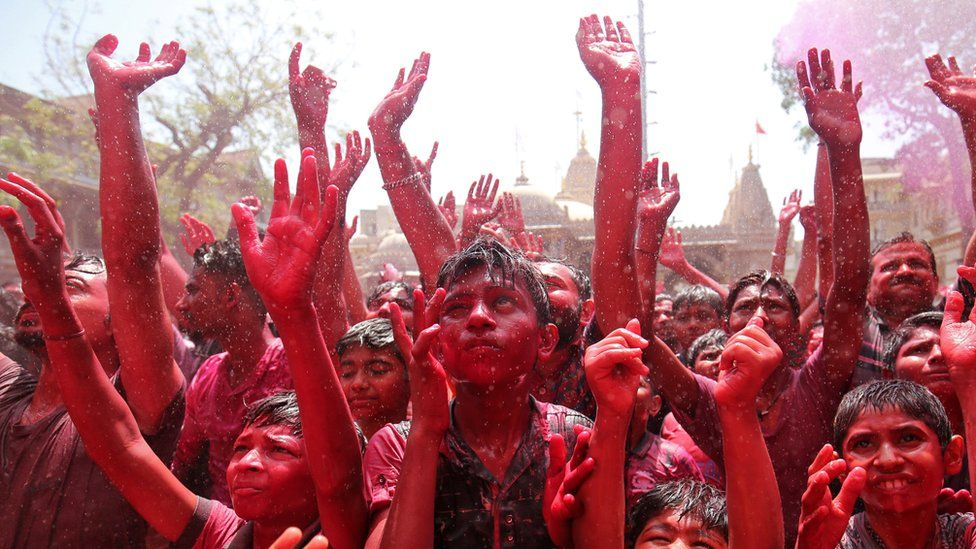 A crowd completely covered in colours hold their hands in the air