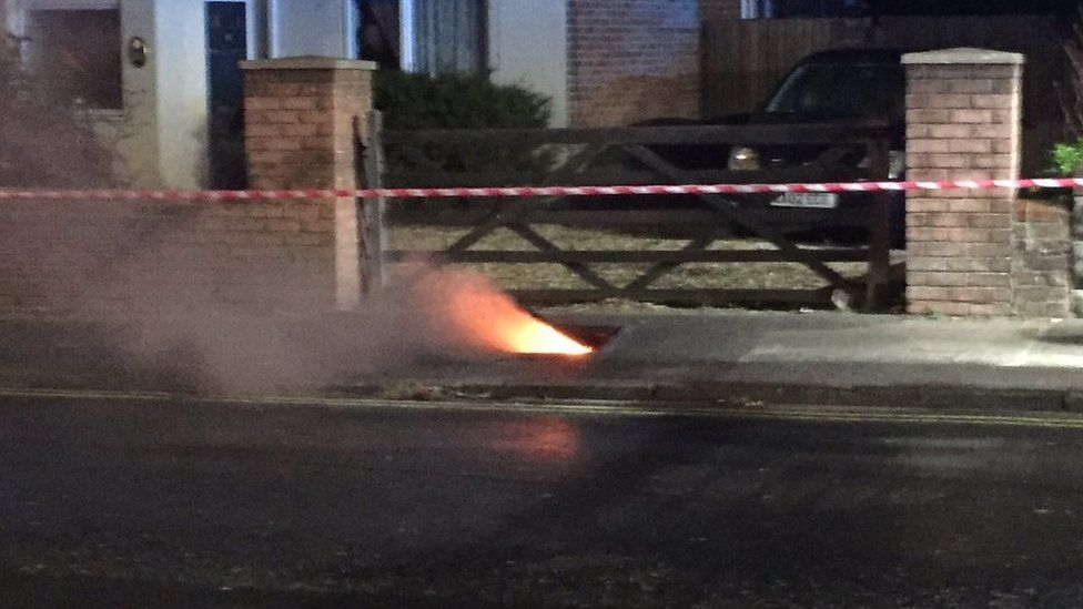 Flames and smoke rising from a manhole