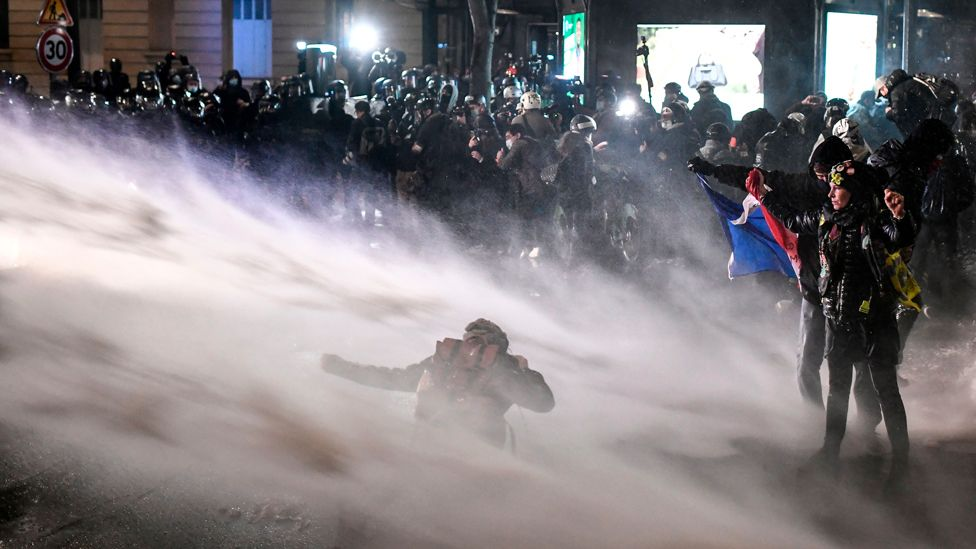 Police spray a water cannon at protesters during a demonstration in Paris