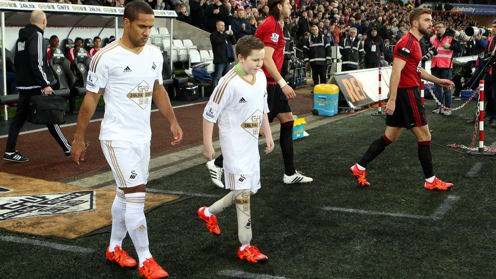 Swansea City mascot with player