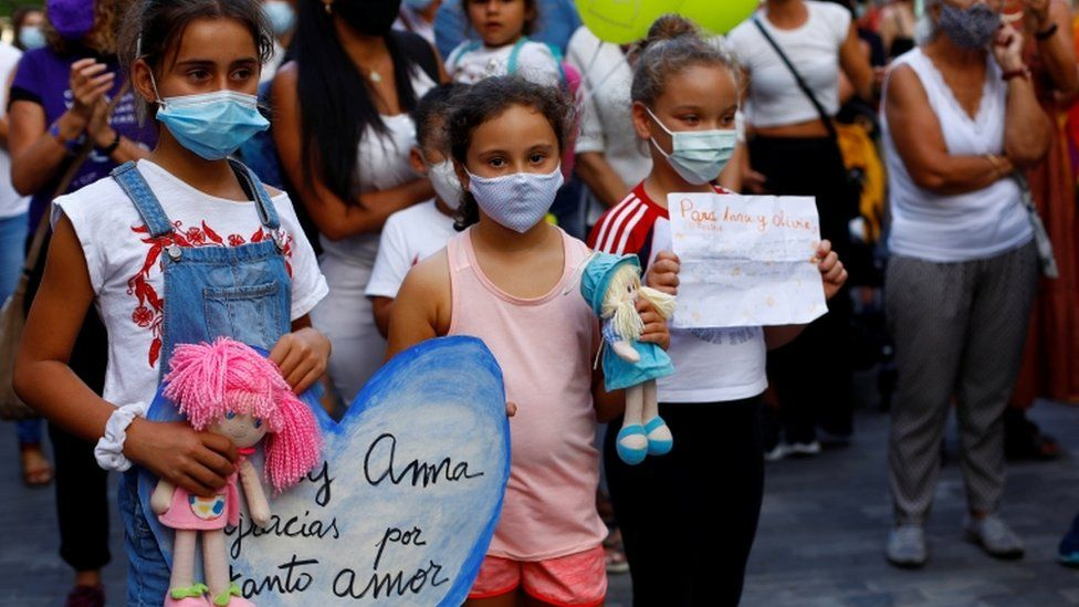 Children at a protest holding dolls and signs