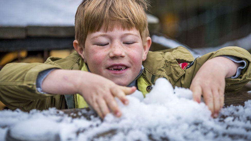 Хлопчик грає зі снігом