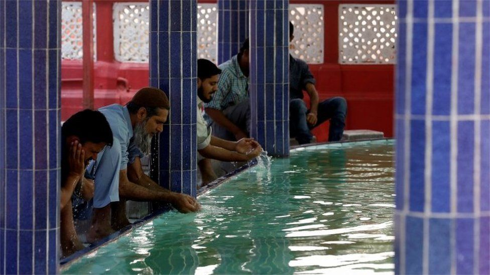 Muslims perform ablution as they gather to attend Friday prayer amid an outbreak of the coronavirus disease (COVID-19), at a mosque in Karachi, Pakistan March 20, 2020