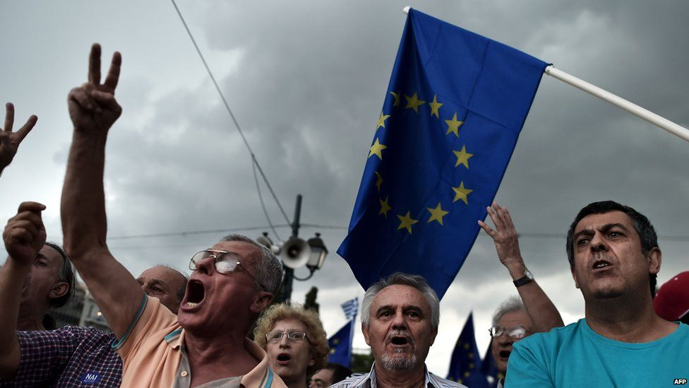 Pro-euro protesters hold European Union flags during a demonstration in front of the parliament in Athens