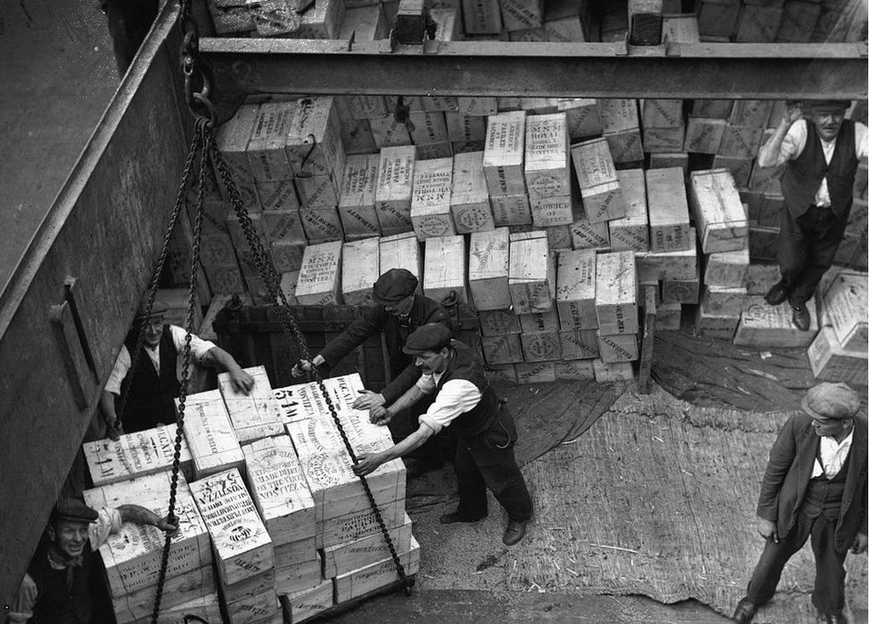 Workmen unloading a consignment of dried fruit from a ship's hold at London Docks in 1930
