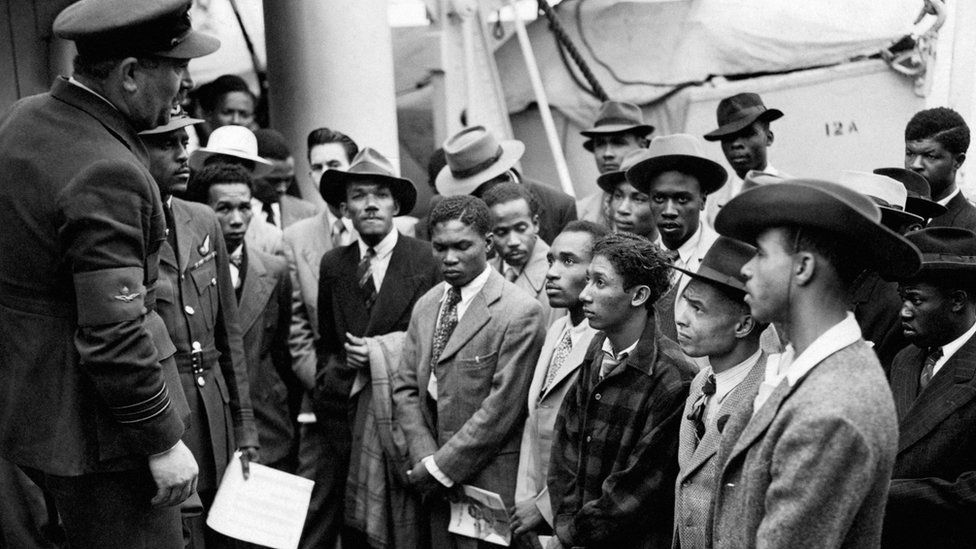 """Jamaican (West Indian) immigrants welcomed by RAF officials from the Colonial Office after the ex-troopship HMT """"Empire Windrush"""" landed them at Tilbury"""
