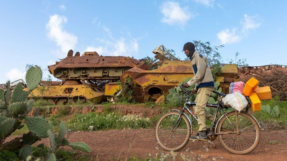 Eritrean man riding a bicycle in front of the military tank graveyard, Central region, Asmara, Eritrea on August 22, 2019 in Asmara, Eritrea.
