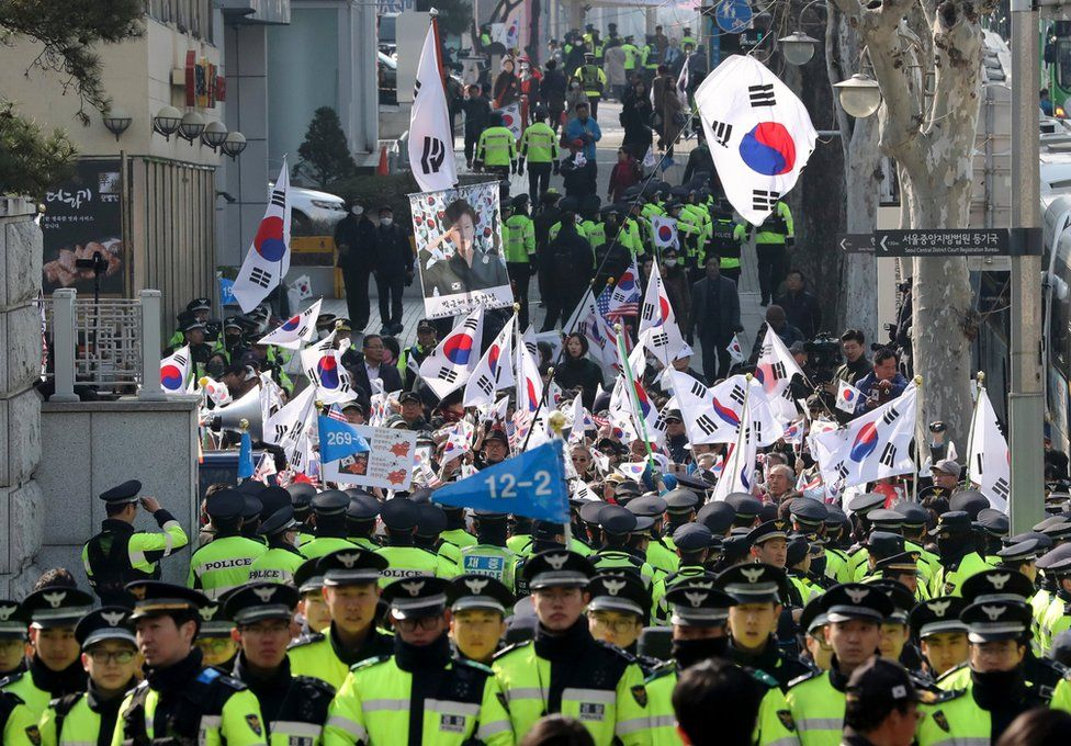 Supporters of South Korean ousted President Park Geun-hye wave national flags and picture of Park outside of a prosecutors' office in Seoul, South Korea, Tuesday, 21 March 2017.