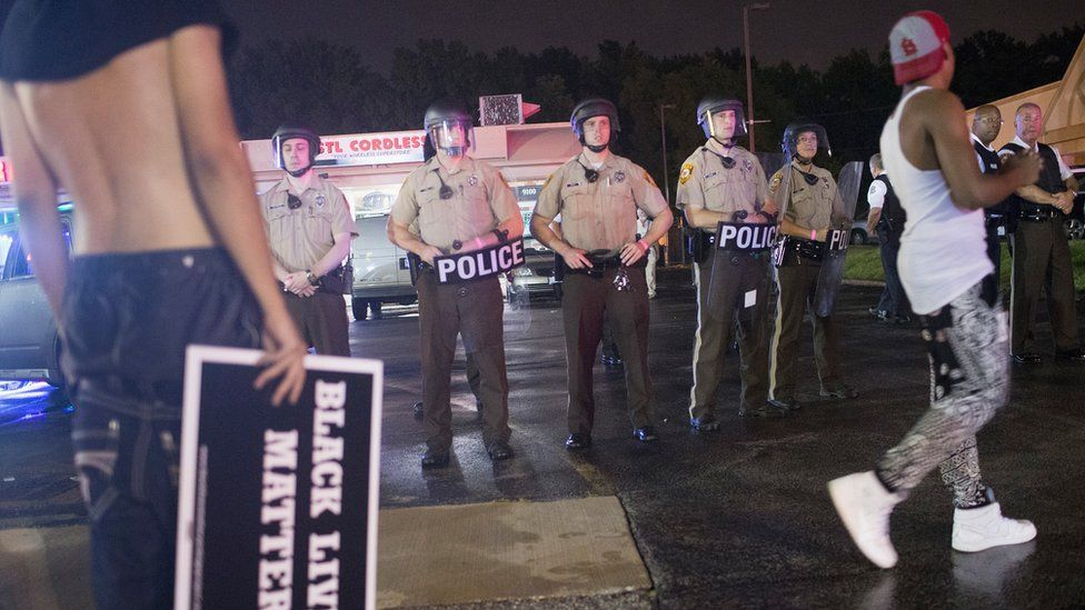 A line of police stand behind protesters in Ferguson, Missouri