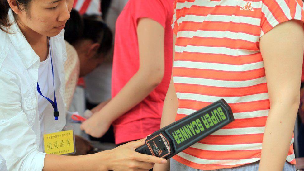 An invigilator (L) checks a student before the 2013 college entrance exam starts in Jilin, northeast China's Jilin province on June 7, 2013.
