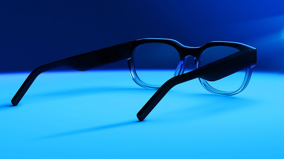 A stock image of North AR glasses on a table lit by blue lights