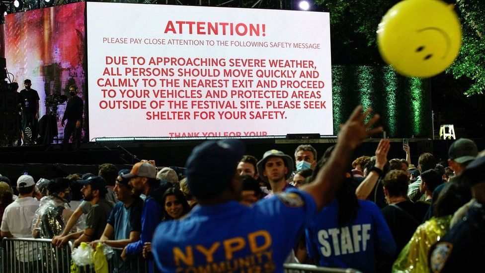 """A screen shows information about severe weather approaching the area as New York police officers try to move people out of the field after cancelling the """"We Love NYC: The Homecoming Concert"""" at Central Park"""
