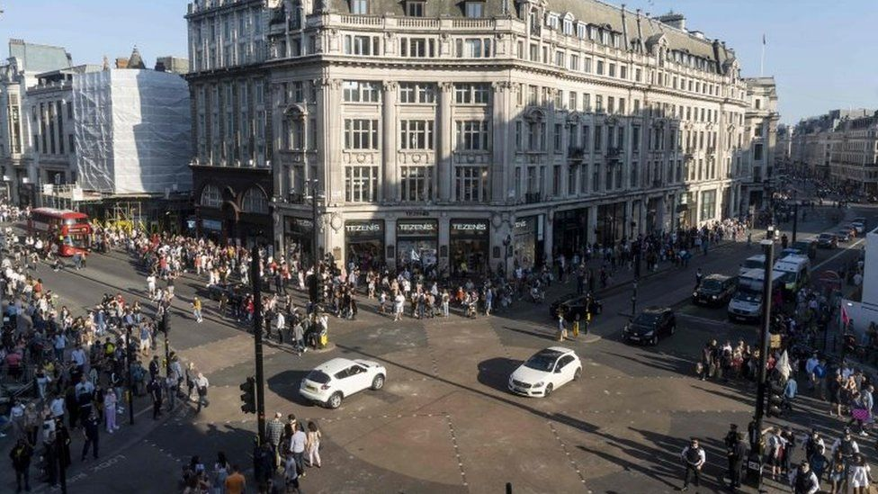Pedestrians and vehicles cross the junction after police cleared climate change activists blocking the road at Oxford Circus
