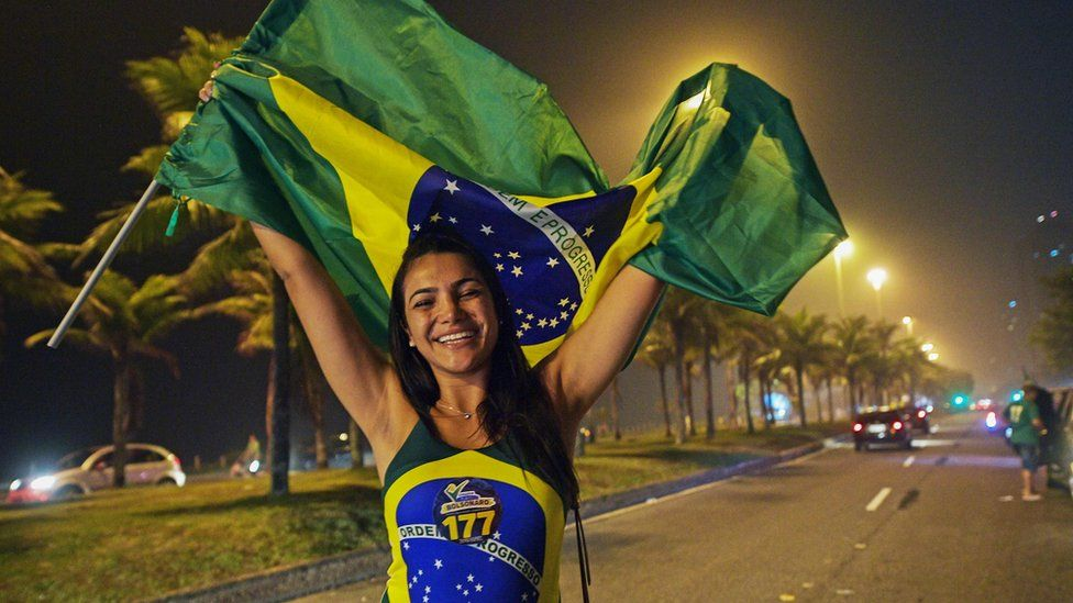 A supporter of Jair Bolsonaro in Brazil celebrates his first round win, dressed up in the flag, October 7 2018