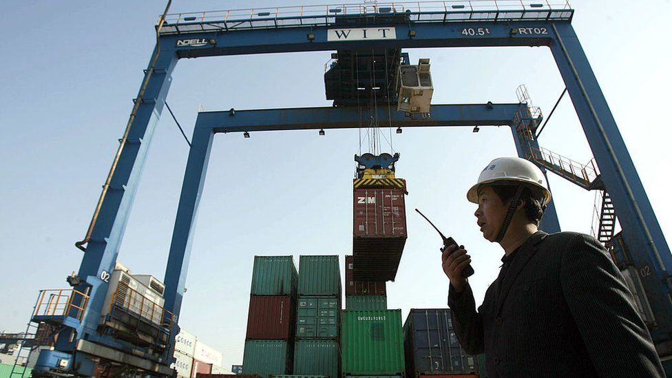 A worker monitors the loading of shipping containers at the container port in Wuhan, in central China
