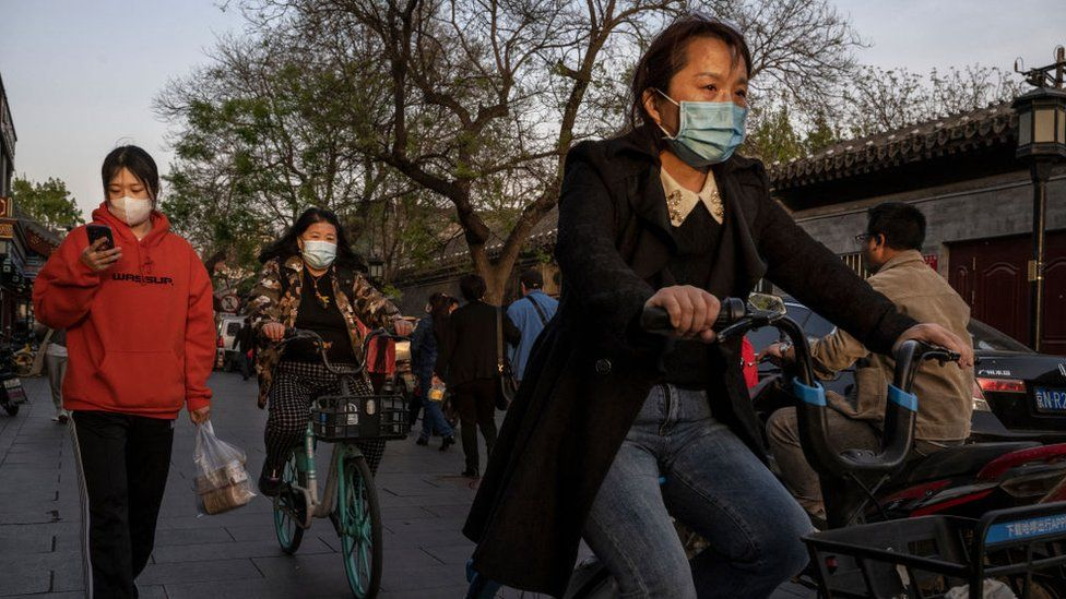 Women wear protective masks as they walk and ride shared bikes in Beijing.