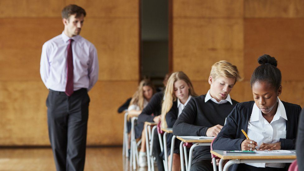 A row of pupils taking exams and a teacher invigilating