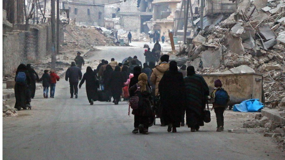 Syrian civilians flee the Sukkari neighbourhood towards safer rebel-held areas in south-eastern Aleppo, on 12 December 2016, during an operation by Syrian government forces to retake the embattled city.
