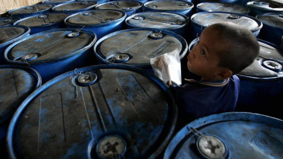 A child refugee from Myanmar plays among oil containers