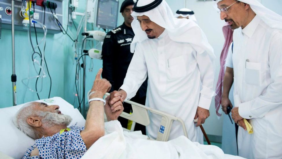 Saudi King Salman holds the hand of an injured pilgrim at a hospital in Saudi Arabia's holy Muslim city of Mecca - 12 September 2015