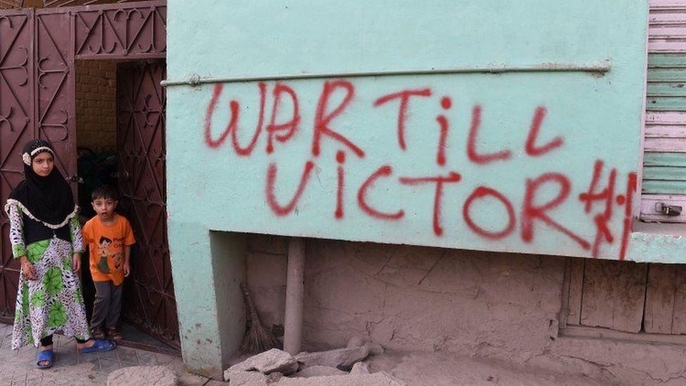 "Indian Kashmiri children stand next to graffiti that reads ""War till Victory"" during a curfew in Srinagar (08 July 2017)"