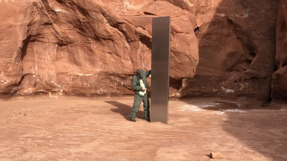 A wildlife official stands by the monolith