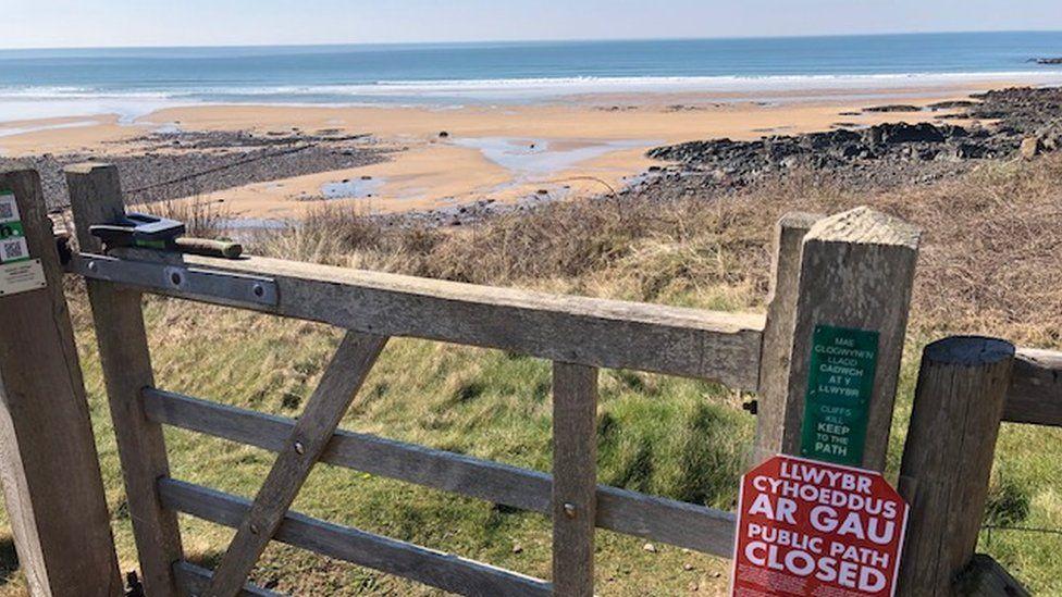 A closed sign on a coastal path gate