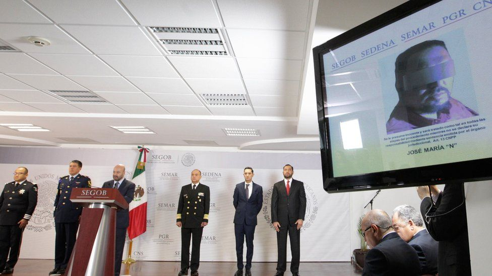 A screen shows a picture of cartel leader Jose Maria Guizar Valencia (R) during a press conference in Mexico City, 9 February 2018
