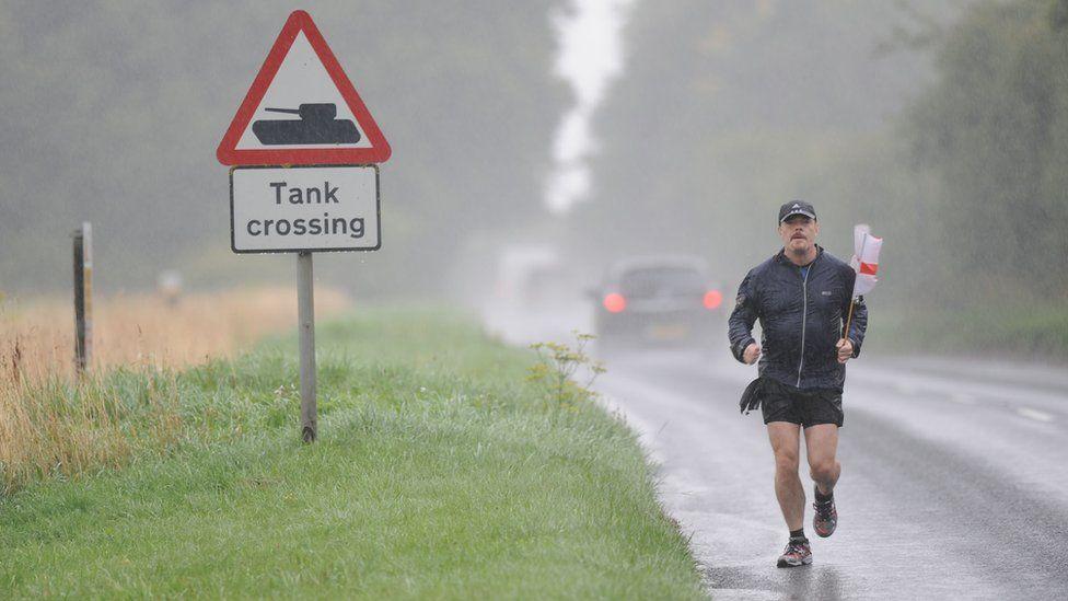 "Eddie Izzard running in rain, holding England flag, past sign reading ""Tank Crossing"""