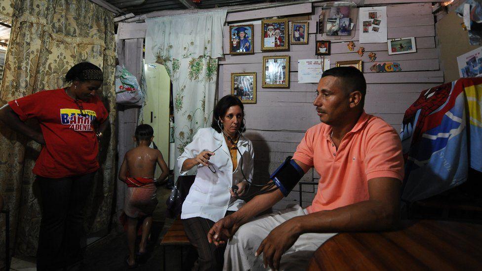 Cuban doctor Nilda Maria Leiseca assists a man at his house in La Vega neighborhood, Caracas