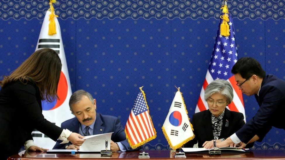 South Korean Foreign Minister Kang Kyung-wha and US ambassador to South Korea Harry Harris, sign documents at the Foreign Ministry in Seoul