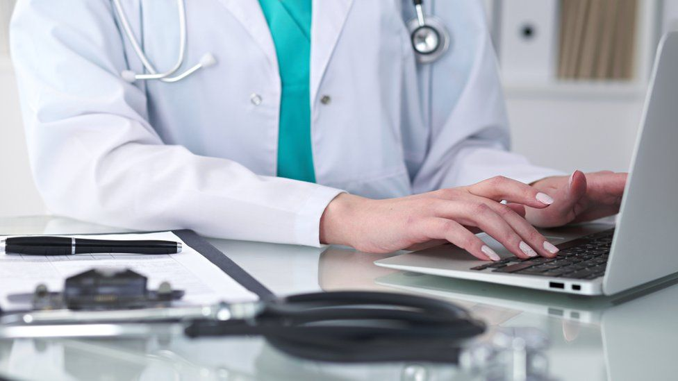 A doctor uses a laptop computer